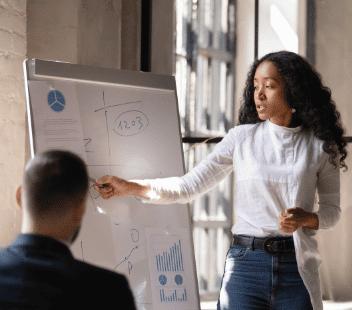 Women talking to man displaying white board