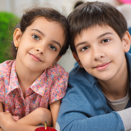 A young boy and girl smiling and looking at the camera