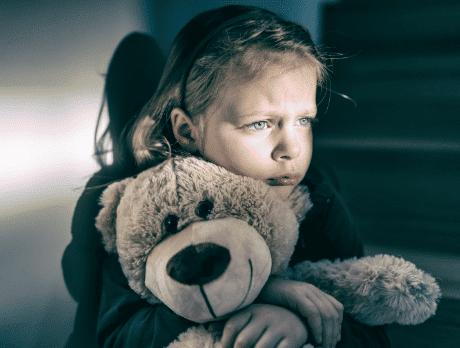 A distressed child hugging a teddy bear