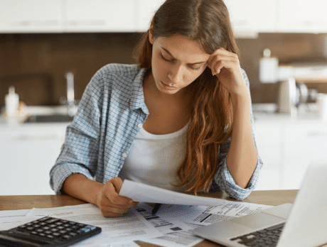 A stressed woman looking at bills